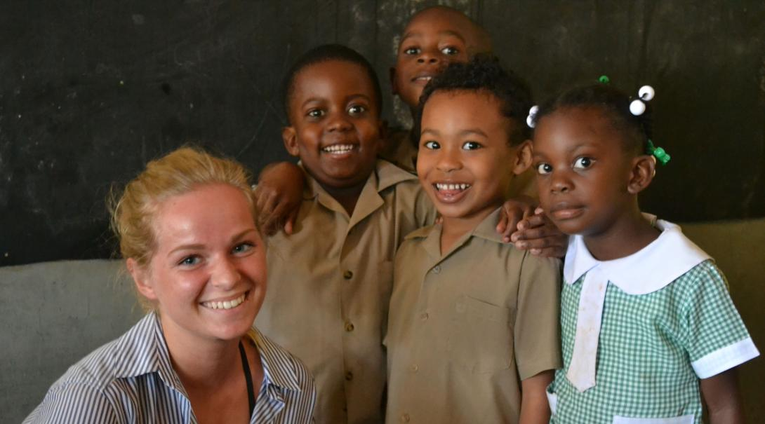 A short term volunteer teaching abroad takes a photo with her students in Jamaica